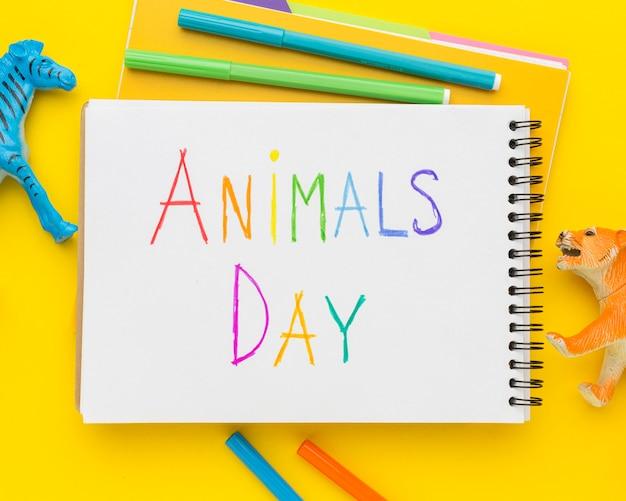 Posição plana de estatuetas de animais e escrita multicolorida no caderno para o dia dos animais