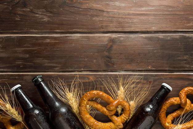 Posição plana de garrafas de cerveja com pretzels e espaço de cópia