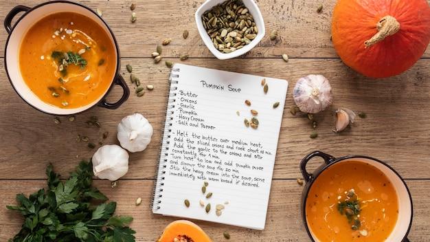 Posição plana de ingredientes alimentares com sopa de abóbora e caderno