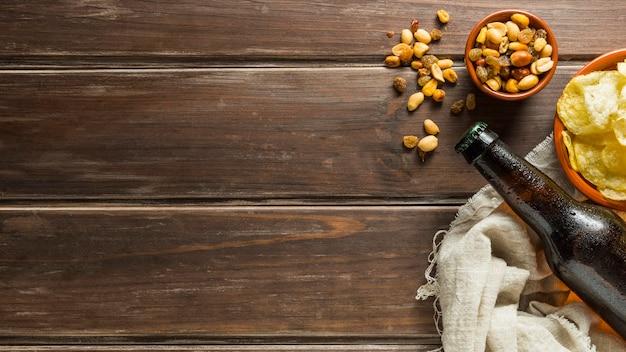 Posição plana de nozes com garrafas de cerveja e batatas fritas