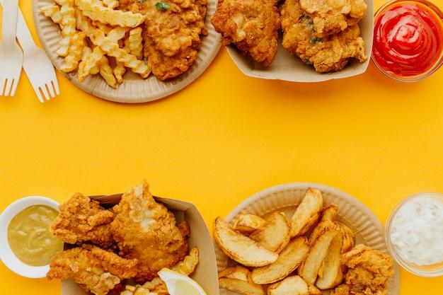 Posição plana de peixe e batatas fritas com espaço de cópia e molhos