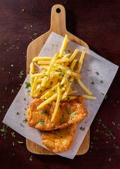 Posição plana de peixe e batatas fritas na tábua de cortar