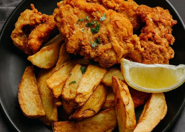 Posição plana de peixe e batatas fritas no prato com rodela de limão