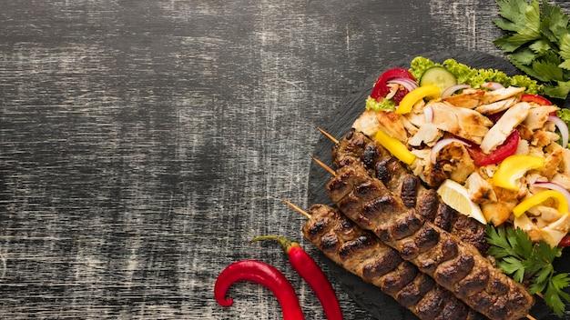 Posição plana de saboroso kebab com espaço de cópia e salada