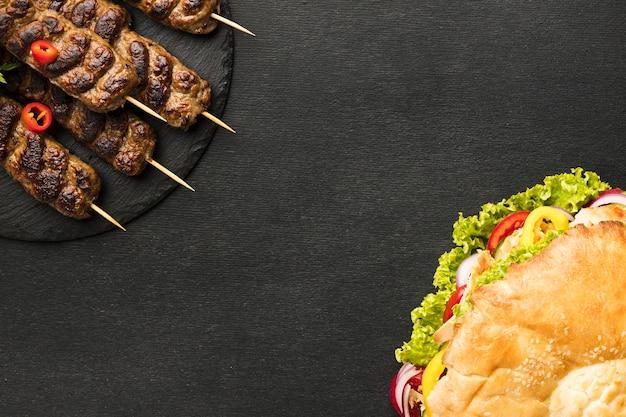 Posição plana de saboroso kebab em ardósia com espaço de cópia