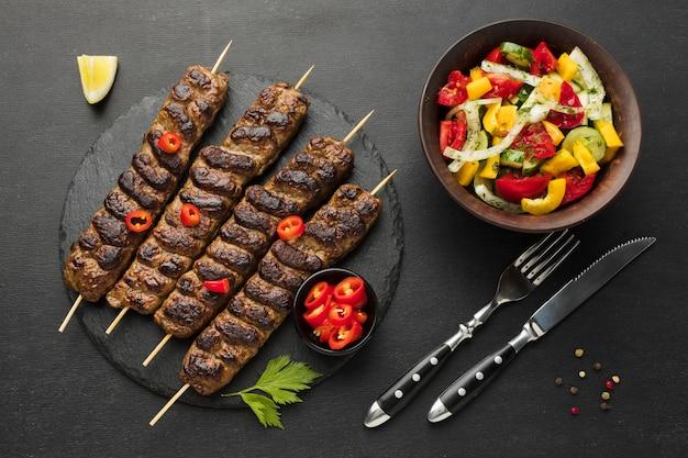 Posição plana de saboroso kebab em ardósia com outro prato e talheres
