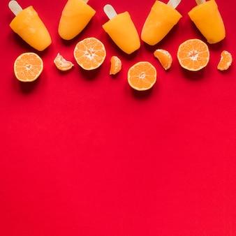 Posição plana de saborosos picolés com espaço de cópia e laranja