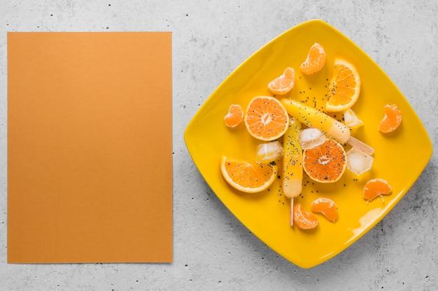 Posição plana de saborosos picolés no prato com laranja e espaço de cópia