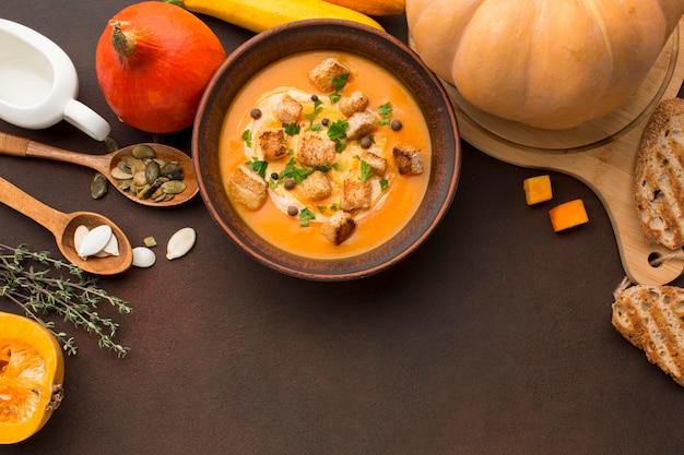 Posição plana de sopa de abóbora com croutons na tigela