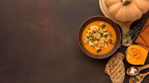 Posição plana de sopa de abóbora com espaço de cópia e croutons na tigela