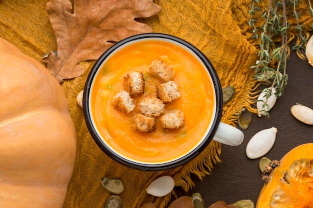 Posição plana de sopa de abóbora em uma caneca com croutons