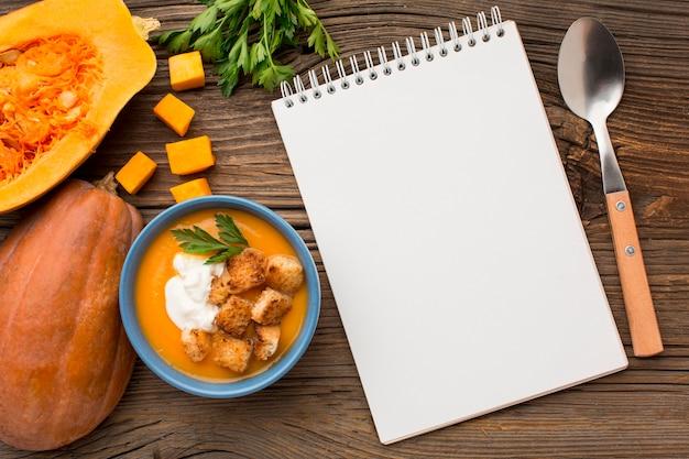 Posição plana de sopa de abóbora em uma tigela com caderno