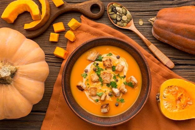 Posição plana de sopa de abóbora em uma tigela com croutons e colher