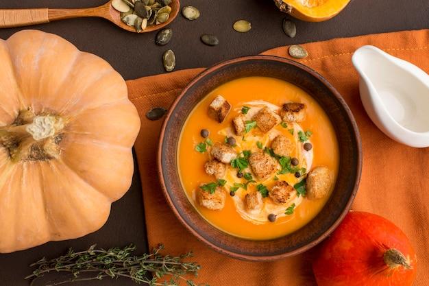 Posição plana de sopa de abóbora em uma tigela com croutons