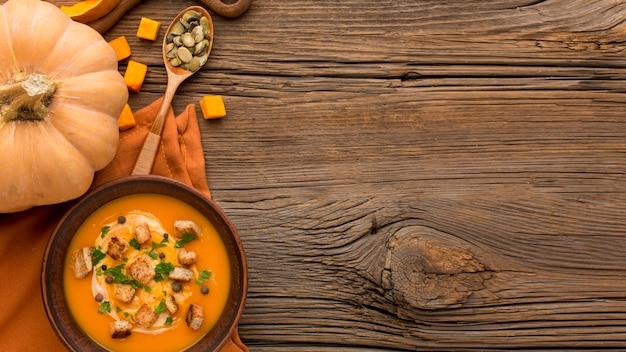 Posição plana de sopa de abóbora em uma tigela com espaço de cópia e croutons