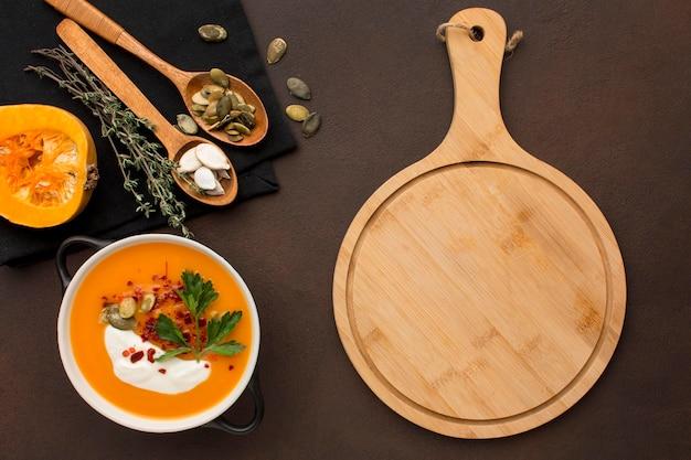 Posição plana de sopa de abóbora em uma tigela com tábua de cortar e colheres