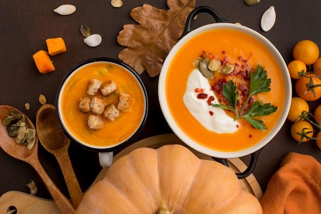 Posição plana de sopa de abóbora em uma tigela e caneca com croutons e salsa