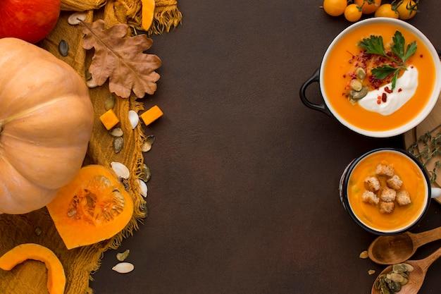 Posição plana de sopa de abóbora em uma tigela e caneca com espaço de cópia e croutons