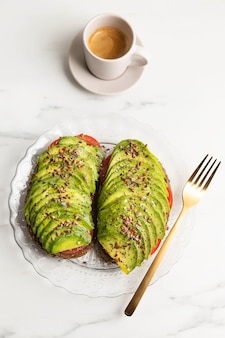 Posição plana de torrada de abacate no prato com talheres e café