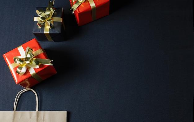 Posição plana de um saco de papel ecológico marrom e caixas de presente de natal com espaço de cópia