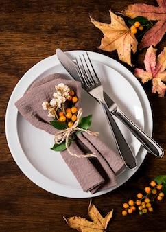 Posição plana do arranjo da mesa de ação de graças com talheres e folhas de outono