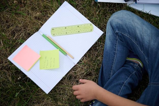 Posição plana do caderno aberto com papéis coloridos com problemas de aritmética, lápis, régua e caneta no meio do caderno deitado na grama verde no parque, o menino do colo sentado ao lado dele fazendo o dever de casa