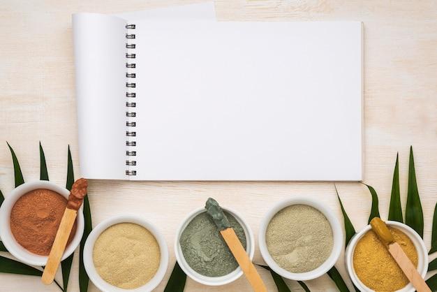 Posição plana do caderno com variedade de tigelas com pó