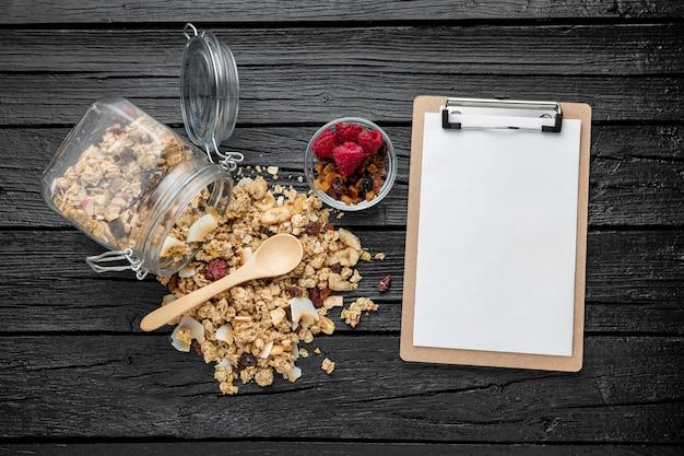 Posição plana do frasco com cereais matinais e bloco de notas