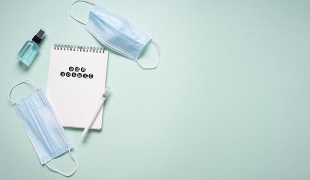 Posição plana do notebook com desinfetante para as mãos e máscaras médicas