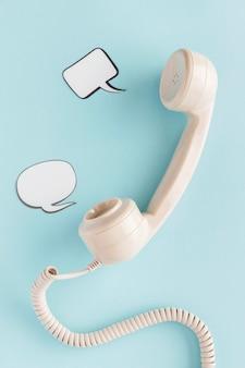 Posição plana do receptor de telefone retrô com bolhas de bate-papo