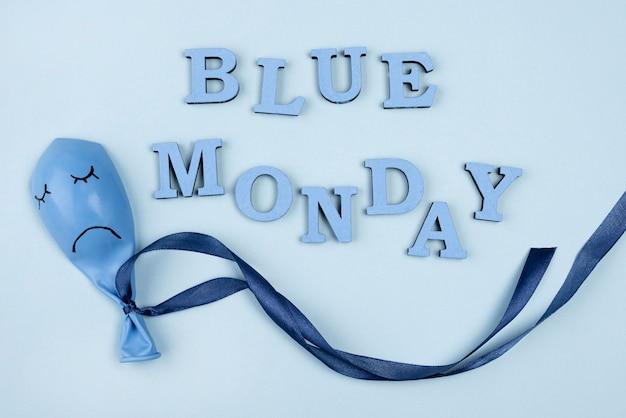 Posição plana do triste balão de segunda-feira azul com fita