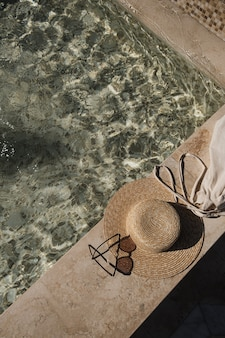 Posição plana dos óculos de sol e chapéu de palha no lado da piscina de mármore com água azul clara com reflexos de sombra de luz solar de ondas