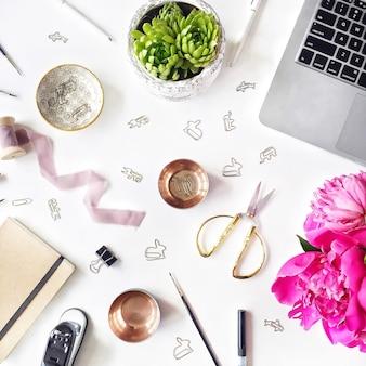 Posição plana no local de trabalho com laptop, suculenta, peônias, tesoura dourada, carretel com fita bege, lápis e diário