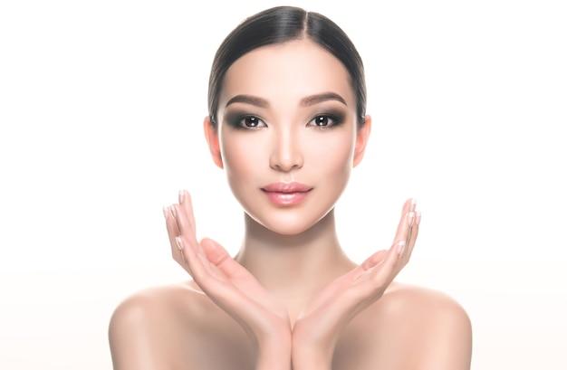 Posição simétrica das mãos em frente ao rosto de uma jovem linda mulher asiática com ombros nus maquiagem delicada com olhos esfumados e lábios rosados tratamento facial cosmetologia beleza e spa