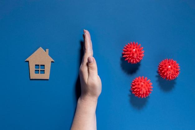 Posicionamento plano da mão protegendo a casa de vírus