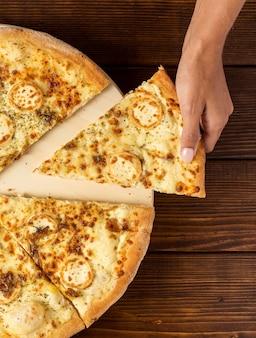Posicione a mão pegando uma fatia de pizza com queijo