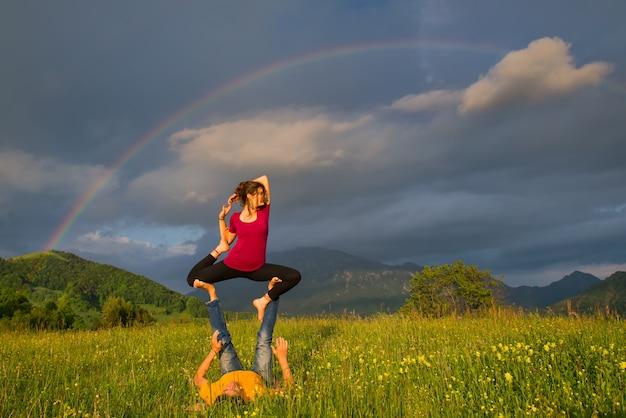 Posições acroyoga garota de homem na natureza nas montanhas com arco-íris no fundo.