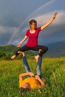 Posições de yoga nas montanhas com arco-íris no fundo