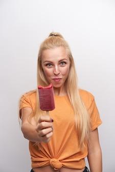 Positiva bela jovem loira com penteado de rabo de cavalo levantando a mão com sorvete mordido e olhando alegremente para a câmera, vestida com roupas casuais sobre fundo branco