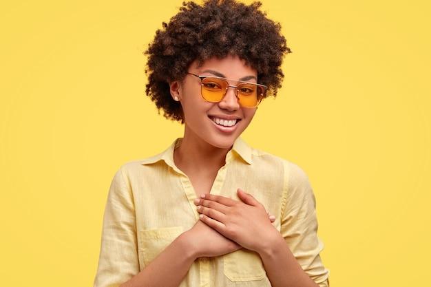 Positiva, feliz e adorável jovem com penteado afro, mantém as mãos no coração, expressa suas emoções e sentimentos sinceros