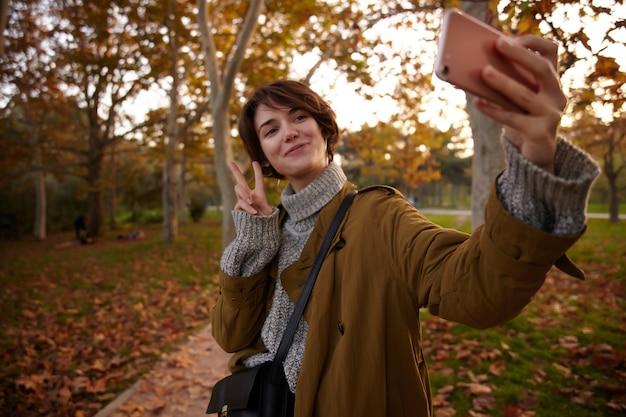 Positiva, jovem adorável morena de cabelos curtos levantando a mão com o símbolo da paz enquanto faz uma foto de si mesma com o celular, posando sobre árvores amareladas no jardim da cidade