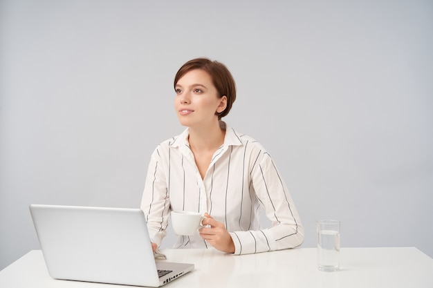 Positiva jovem adorável mulher de cabelos castanhos com corte de cabelo curto na moda, olhando sonhadoramente para a frente enquanto toma uma xícara de chá durante o dia de trabalho, sentada à mesa no branco