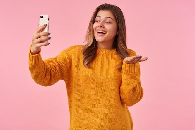 Positiva, jovem adorável mulher de cabelos castanhos com maquiagem natural, levantando a mão com o celular enquanto faz selfie, sorrindo agradavelmente com a palma levantada enquanto posa na rosa