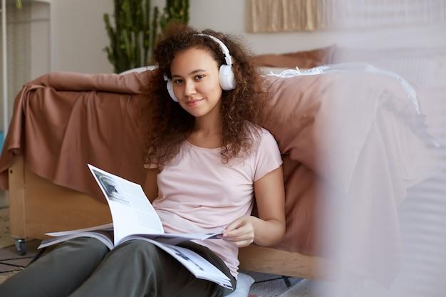 Positiva jovem afro-americana com cabelos cacheados localização na sala, curtindo sua música favorita em fones de ouvido, lendo nova revista, sorrindo e olhares.