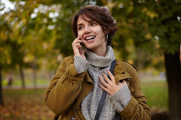 Positiva, jovem atraente morena de cabelos curtos, vestida com roupas da moda, olhando alegremente para o lado e sorrindo amplamente, tendo uma boa conversa ao telefone enquanto está sobre o parque desfocado