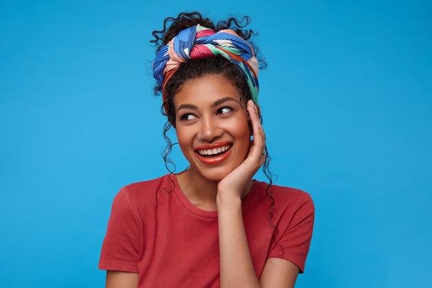 Positiva jovem atraente morena encaracolada com bandana multicolorida, apoiando o queixo na mão levantada enquanto olha para o lado com um sorriso agradável, posando sobre a parede azul