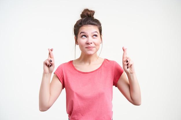 Positiva jovem bonita de cabelos castanhos com maquiagem natural, levantando as mãos com os dedos cruzados e sorrindo alegremente em pé sobre um fundo branco