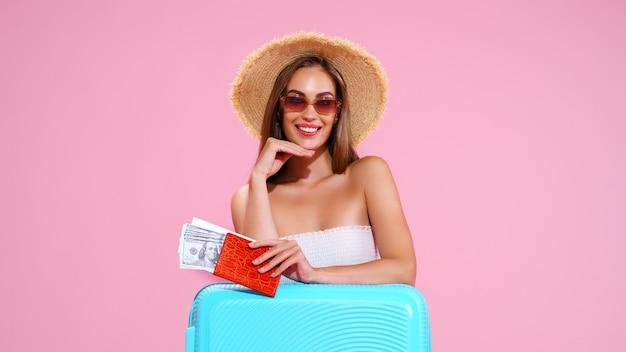 Positiva jovem com chapéu de palha e óculos escuros com ingressos e mala rosa fundo estúdio smi.