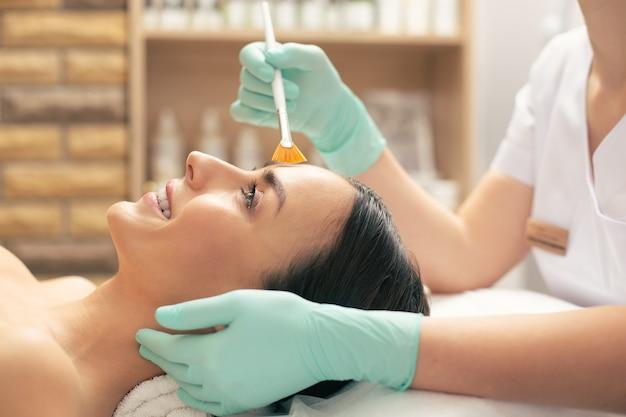 Positiva jovem de cabelos escuros deitada sobre a toalha branca e as mãos da esteticista em luvas de borracha, realizando o peeling no rosto