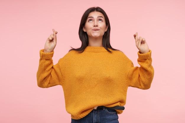Positiva, jovem e adorável mulher de cabelos castanhos mordendo o lábio de forma preocupante enquanto olha para cima e levanta as mãos com os dedos cruzados, em pé sobre a parede rosa